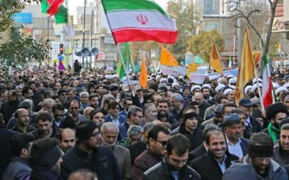 "Iranians wave national flags during a protest in support of the Islamic Republic's government and supreme leader, Ayatollah Ali Khamenei, in the northwestern city of Ardabil on November 20, 2019, as President Hassan Rouhani says the country's people had defeated an ""enemy conspiracy"" behind a wave of violent street protests. (STR/AFP)"