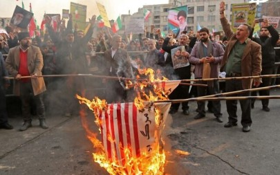 "Iranian pro-government demonstrators burn makeshift US flags as they gather in the capital Tehran's central Enghelab Square on November 25, 2019, to condemn days of ""rioting"" that Iran blames on its foreign foes. (ATTA KENARE / AFP)"