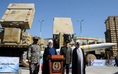 President Hassan Rouhani, second left, speaks during a ceremony to unveil the Iran-made Bavar-373, a long-range surface-to-air missile system, displayed at rear, as his Defense Minister Gen. Amir Hatami, second right, commander of army's air defense force Gen. Alireza Sabahifard, left, and the chairman of the parliament's National Security and Foreign Policy Committee Mojtaba Zolnour, listen, at an undisclosed location in Iran,, August 22, 2019. (Iranian Presidency Office via AP)