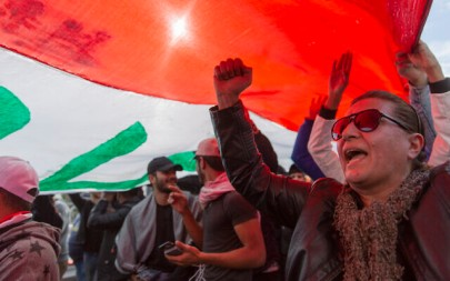 Anti government protesters chant anti-Iran and anti-US slogans under a big Iraqi flag that they carry during the ongoing protests in Tahrir square, Baghdad, Iraq, Friday, Jan. 10, 2020. (AP Photo/Nasser Nasser)