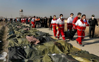 Rescue workers carry the body of a victim of a Ukrainian plane crash in Shahedshahr, southwest of Tehran, Iran, January 8, 2020 (AP/Ebrahim Noroozi)