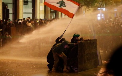 Anti-government protesters wave a Lebanese flag and hide behind a wood barrier from a water cannon as they clash with the riot police during a protest against the new government, near the parliament square, in Beirut, Lebanon, Wednesday, Jan. 22, 2020. (AP/Hussein Malla)