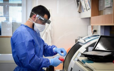 Medical team members at the Barzilay hospital, in the southern Israeli city of Ashkelon, wear protective gear, as they handle a coronavirus test sample on March 29, 2020. (Flash90)