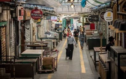 People walk through Jerusalem's mostly shuttered Mahane Yehuda Market on April 16, 2020. (Yonatan Sindel/Flash90)