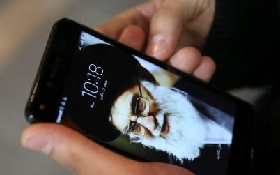 A Tehran resident, Hamed Ghassemi, looks at his cellphone, with a portrait of Iranian Supreme Leader Ayatollah Ali Khamenei. (AP Photo/Vahid Salemi)