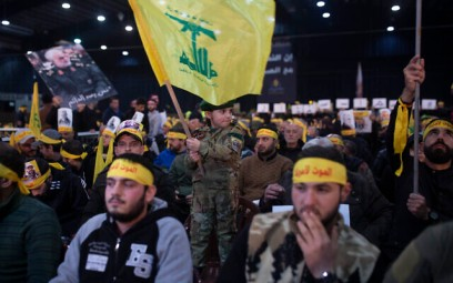 A child in tiny military fatigues waves the Hezbollah flag as supporters of the group's leader Sayyed Hassan Nasrallah wait for his televised speech in a southern suburb of Beirut, Lebanon, Sunday, Jan. 5, 2020 following the US airstrike in Iraq that killed Iranian Revolutionary Guard Gen. Qassem Soleimani. (AP Photo/Maya Alleruzzo)