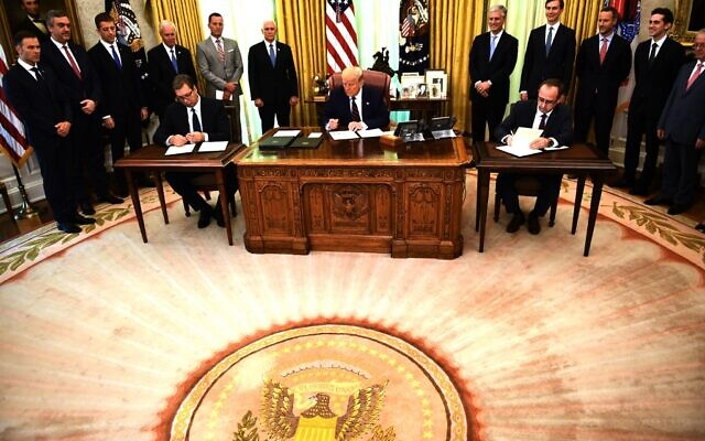 US President Donald Trump signs a document as Kosovar Prime Minister Avdullah Hoti (R) and Serbian President Aleksandar Vucic (L)  sign an agreement on opening economic relations, in the Oval Office of the White House in Washington, DC, on September 4, 2020. (Photo by Brendan Smialowski / AFP)