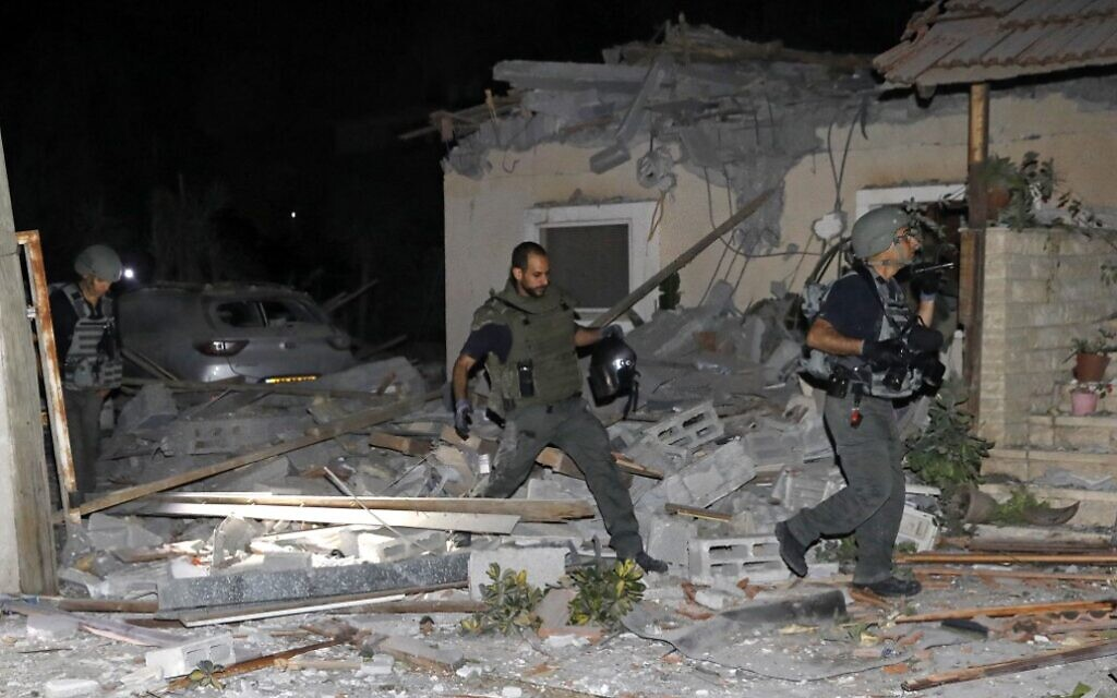 Israeli firefighters and security forces inspect damage to a house hit by a rocket fired from Gaza on May 12, 2021 ( GIL COHEN-MAGEN / AFP)