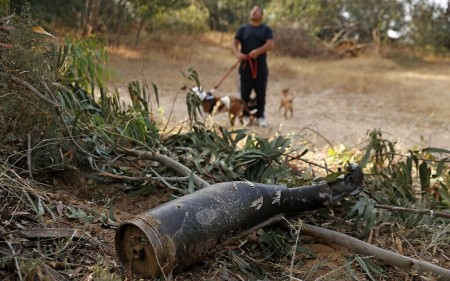 An Israeli man walks past the remains of a rocket fired by the Palestinian Hamas terror group from the Gaza Strip, which was destroyed by Israel's Iron Dome aerial defense system, on May 12, 2021 in Ashkelon (JACK GUEZ / AFP)