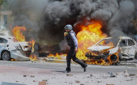 An Israeli firefighter walks next to cars hit by a rocket fired from Gaza Strip, in the southern Israeli town of Ashkelon, May 11, 2021. (AP Photo/Ariel Schalit)