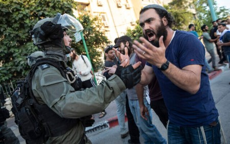 Israeli riot police face off with a Jewish man as clashes erupted between Arabs, police and Jews, in the mixed town of Lod, central Israel, Wednesday, May 12, 2021. (AP Photo/Heidi Levine)