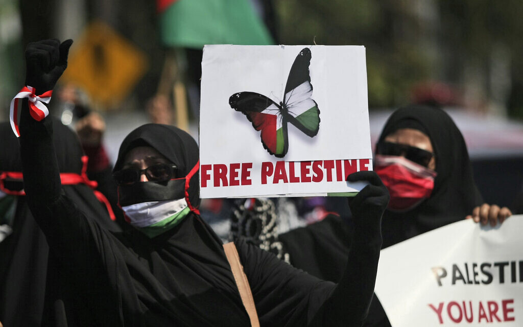 A Muslim women hold posters and shout slogans during an anti-Israel protest in Surabaya, East Java, Indonesia, May 17, 2021. (AP Photo/Trisnadi)