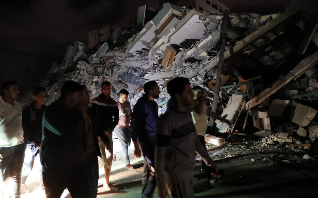 Palestinians pass by the rubble of a destroyed building in Gaza City, May 21, 2021. (AP Photo/Adel Hana)