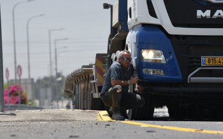 Truck driver shelters during a rocket siren near Ashkelon, May 12, 2021 (Gili Yaari/Flash90)