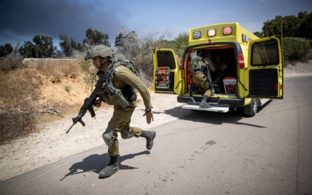 Israeli soldiers near the site of where a jeep went up in flames, injuring 2 and killing one, following a direct hit by a missile fired from Gaza, in Netiv Ha'asara, May 12, 2021 (Yonatan Sindel/Flash90)