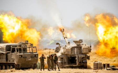 IDF artillery seen firing into Gaza near the Israeli border with the Strip on May 12, 2021, following heavy rocket and missile barrage fired into Israel, May 12, 2021 (Yonatan Sindel/Flash90)