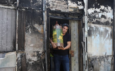 Man carries a Torah scroll from a torched synagogue in the central Israeli city of Lod, following a night of heavy rioting on May 12, 2021 (Yonatan Sindel/Flash90)
