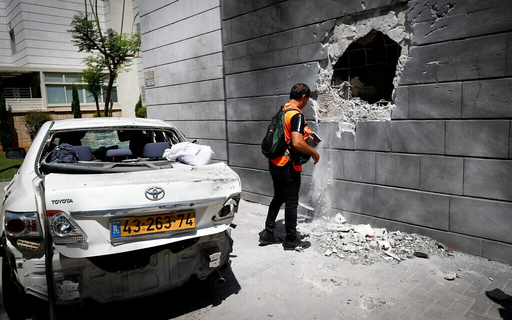 A man inspects damage caused to a building in the southern coastal city of Ashkelon, after it was hit by a rocket fired by Palestinian terrorists in the Gaza Strip, May 14, 2021. (Yonatan Sindel/Flash90)