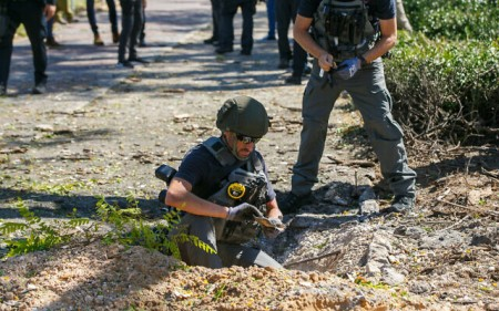 Israeli security forces at the scene where a fragment of a rocket fired from the Gaza Strip landed in the southern Israeli city of Ashdod, on May 19, 2021. (Flash90)